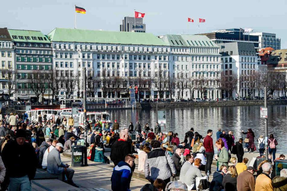 Zahlreiche Menschen genießen das sonnige Wetter am Jungfernstieg in Hamburg.