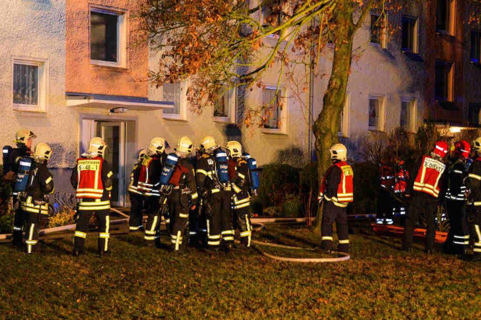 Feuerwehrleute stehen vor dem Hauseingang.