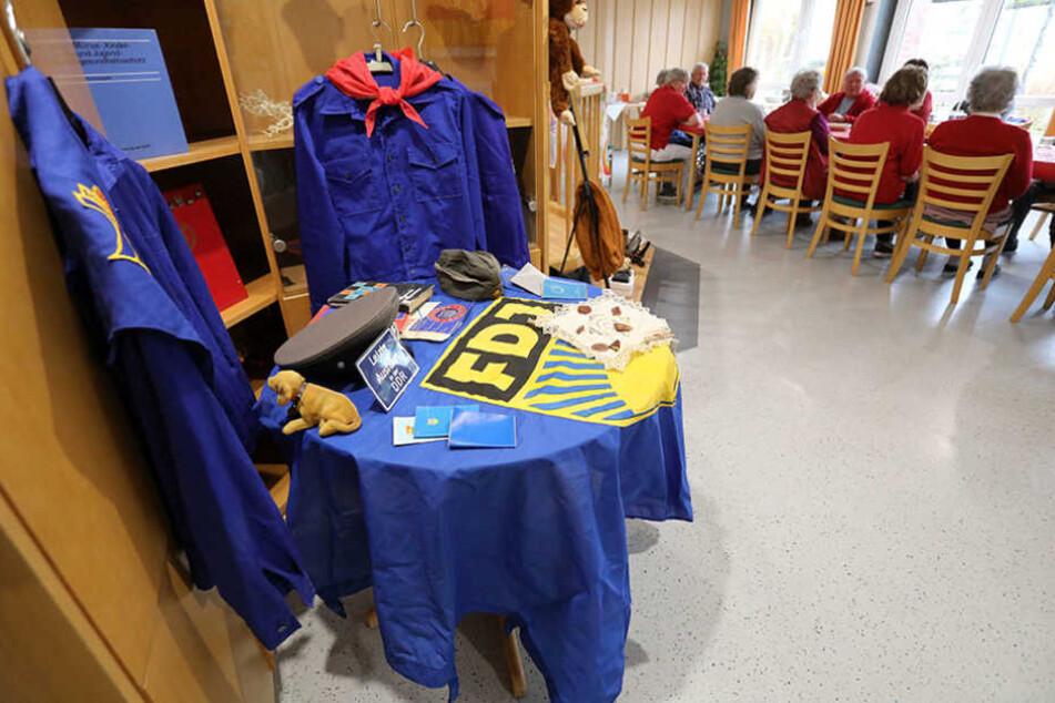 """Bei einem """"Museumstag"""" im DRK-Seniorenheim in Teterow hängen und liegen Pionier-Blusen, FDJ-Blusen, FDJ-Fahnen und andere DDR-Utensilien auf einem Tisch im Raum."""