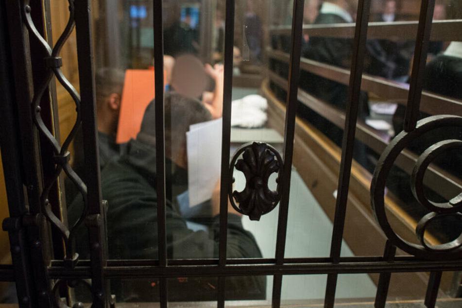 Die Angeklagten verdecken im Kriminalgericht in Berlin-Moabit mit einem Zettel ihr Gesicht. (Archivbild)