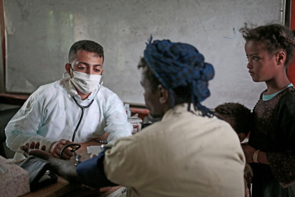 Jemen, Sanaa: Ein Arzt misst den Blutdruck eines Mannes bei einer Wohltätigkeitskampagne in einer Schule von Ärzten zur kostenlosen Gesundheitsvorsorge für ärmere Familien während der Corona-Pandemie.