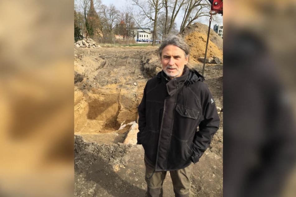 Fred Tribanek vom Munitionsbergungsdienst M.-V. steht vor einem tiefen Loch in der Rostocker Innenstadt in dem eine 250 Kilogramm-Fliegerbombe liegt, die mit Plastik abgedeckt wurde.