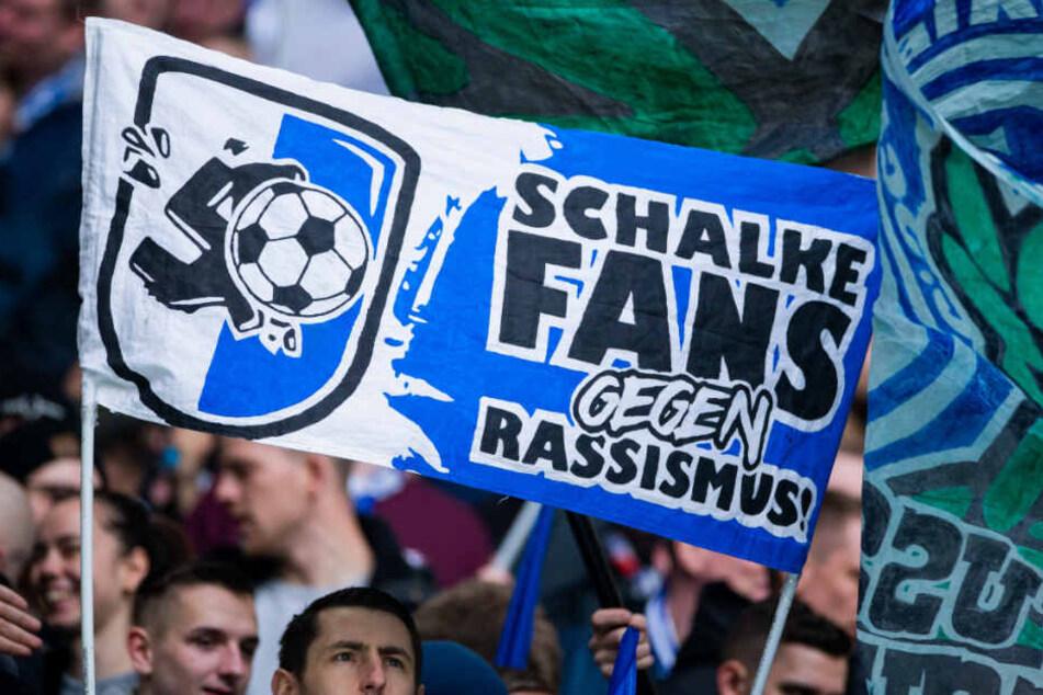 """Die meisten Schalke-Fans haben in der Folge ein Zeichen gegen Rechts gesetzt. Hier ein Gelsenkirchen-Anhänger, der ein Plakat mit der Aufschrift """"Schalke Fans gegen Rassismus!"""" zeigt."""