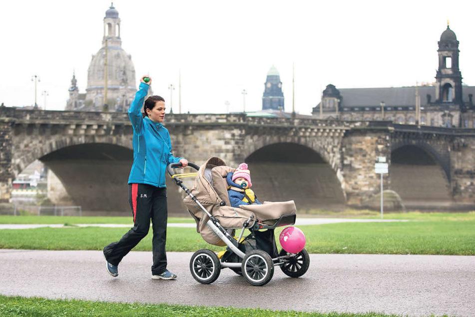 Linke Hand am Kinderwagen, rechter Arm in der Luft: Silke Meißner (30) mit  Tochter Lea (14 Monate) bei einer Übung zum Aufwärmen.