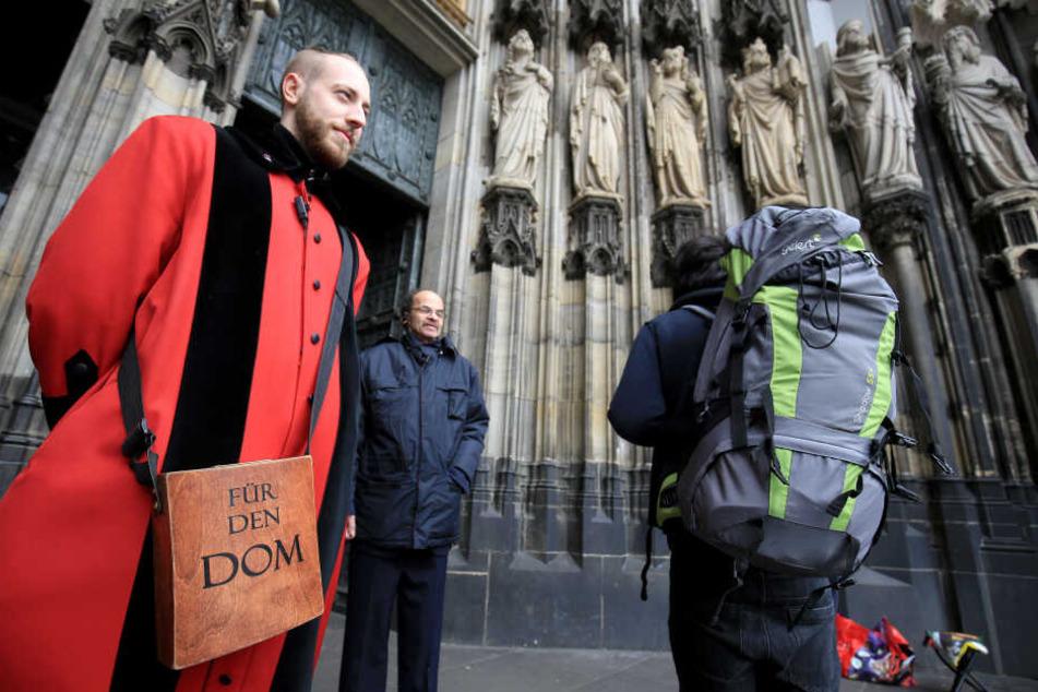 Ein Domschweizer bewacht den Kölner Dom.