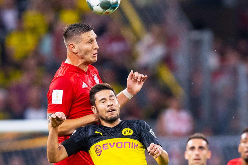 BVB-Kicker Raphael Guerreiro (unten) bei seinem bisher einzigen Pflichtspieleinsatz der Saison im Supercup gegen den FC Bayern München und Niklas Süle.