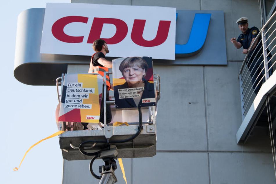 Ein Demonstrant bringt das CDU-Logo mit einer Hebebühne an der CSU-Zentrale an.