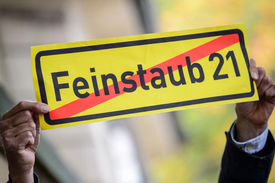 """Ein Mann hält in Stuttgart vor dem Amtssitz von Ministerpräsident Kretschmann ein Schild mit der Aufschrift """"Feinstaub 21 (durchgestrichen) hoch. (Archivbild)"""