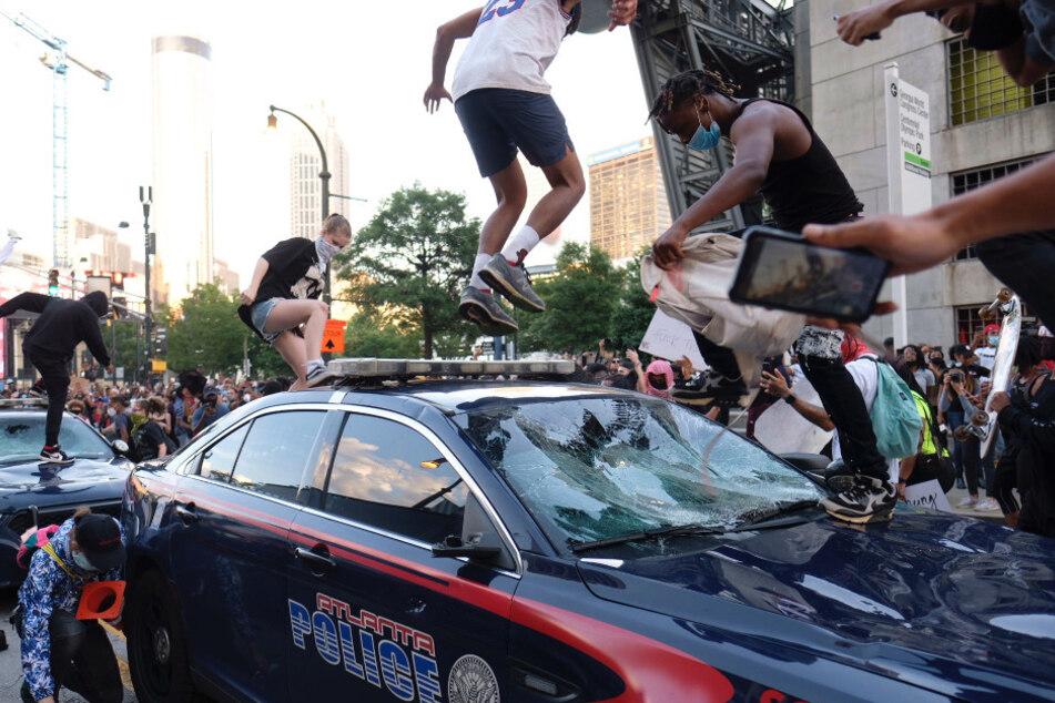 Wütende Demonstranten klettern vor einem Gebäude des Senders CNN auf ein Auto der Polizei und zerstören es.