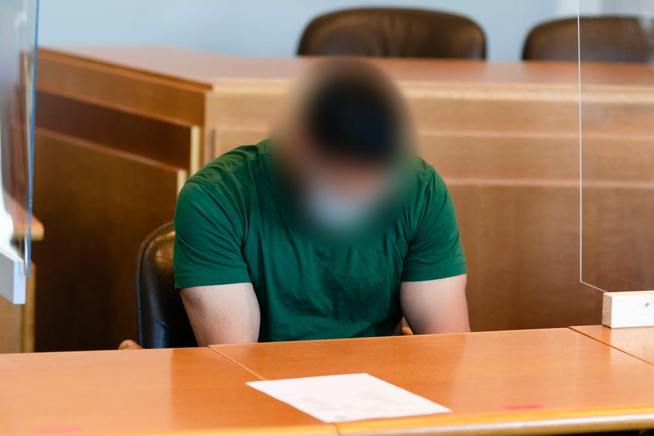 Zum Prozessauftakt wegen Totschlags sitzt der Angeklagte mit gesenktem Kopf, Brille und Nasen-Mund-Schutz im Verhandlungssaal im Landgericht Kiel.