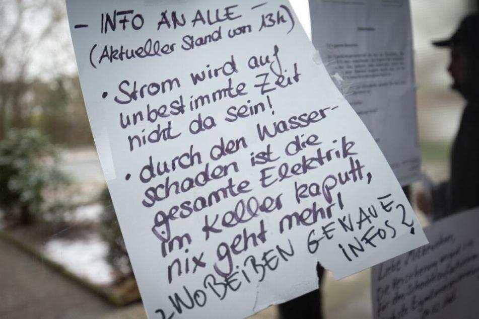Ein Zettel im Hausflur informiert die Bewohner über den Zustand ihrer Hauses.