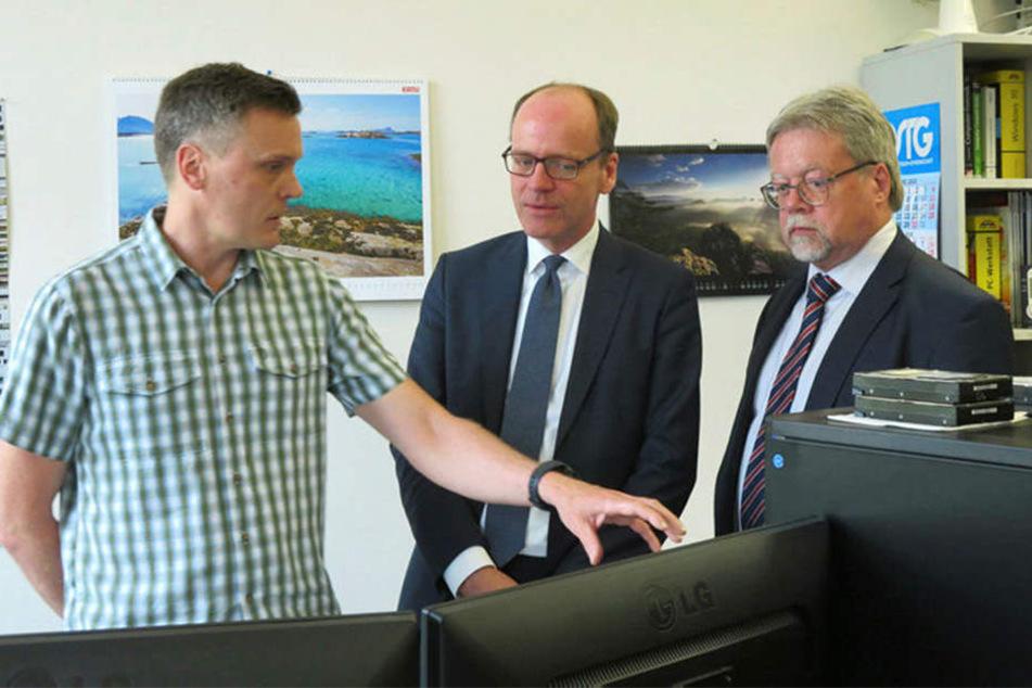 Zwei Steuerfahnder erklären Finanzminister Matthias Haß (51, CDU, Mitte) in ihrer Leipziger IT-Zentrale, wie sie Steuerhinterziehern auf die Schliche kommen.