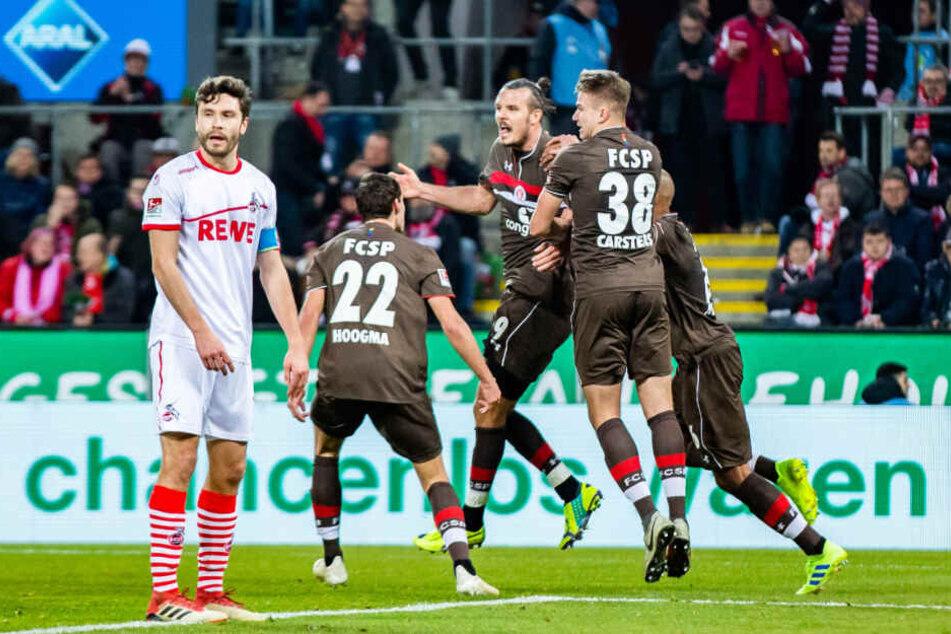 Kölns Jonas Hector (links) konnte nur zusehen, wie sich der FC St. Pauli und Torschütze Alex Meier (Mitte) über dessen Treffer freuten.