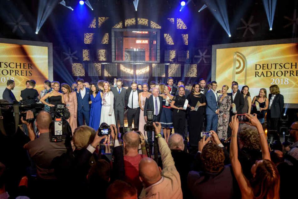Die Preisträger und Laudatoren stehen für ein Gruppenbild auf der Bühne, während die Presse und Gäste versuchen den schönsten Schnappschuss zu ergattern.