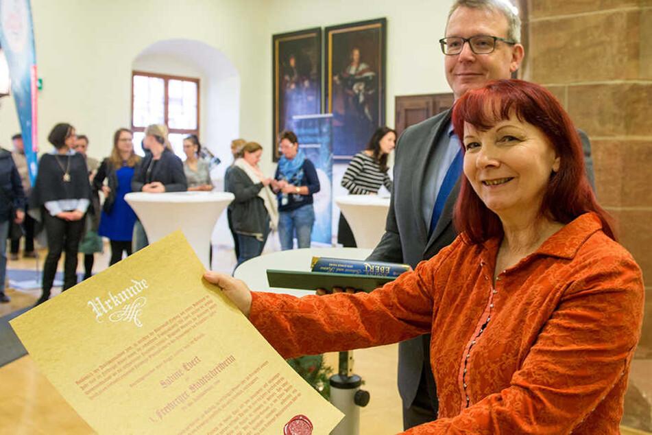 Autorin Sabine Ebert (59) zeigt stolz ihre Bestellungsurkunde als erste Stadtschreiberin von Freiberg.