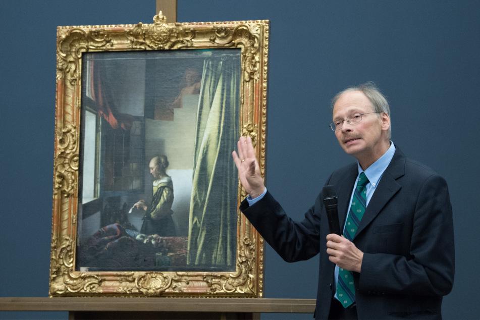 """Christoph Schölzel, Restaurator der Gemäldegalerie Alte Meister, steht während einer Pressekonferenz neben dem Gemälde """"Brieflesendes Mädchen am offenen Fenster"""" von Johannes Vermeer."""