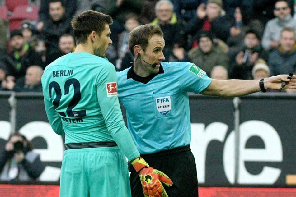 Schiedsrichter Sascha Stegemann (r.) stellt Herthas Torwart Rune Jarstein vom Platz.