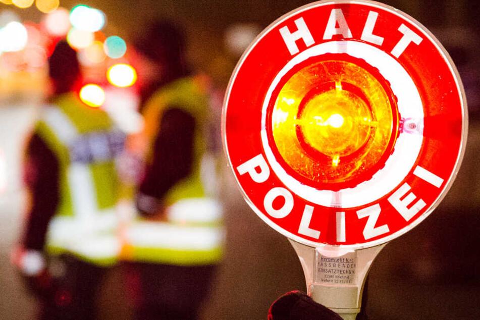 """Ein Polizist hält bei einer Verkehrskontrolle in Hamburg eine Kelle mit der Aufschrift """"Halt Polizei"""" hoch (Symbolbild)."""