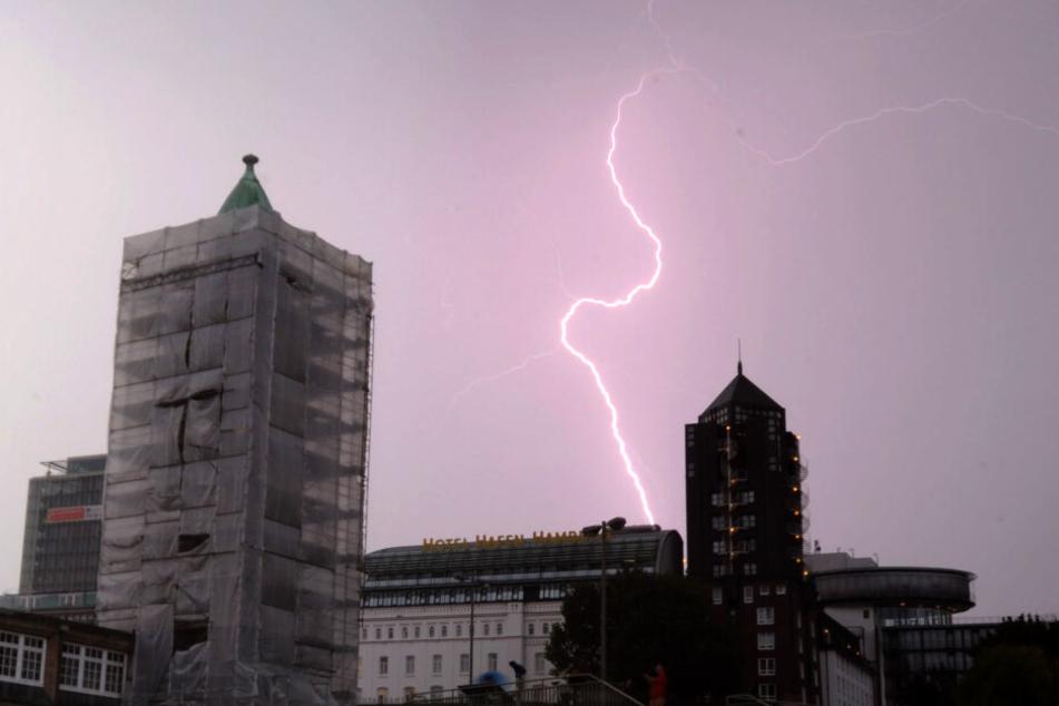 Ein Blitz zuckt während eines Gewitters bei den Landungsbrücken in Hamburg am Himmel.