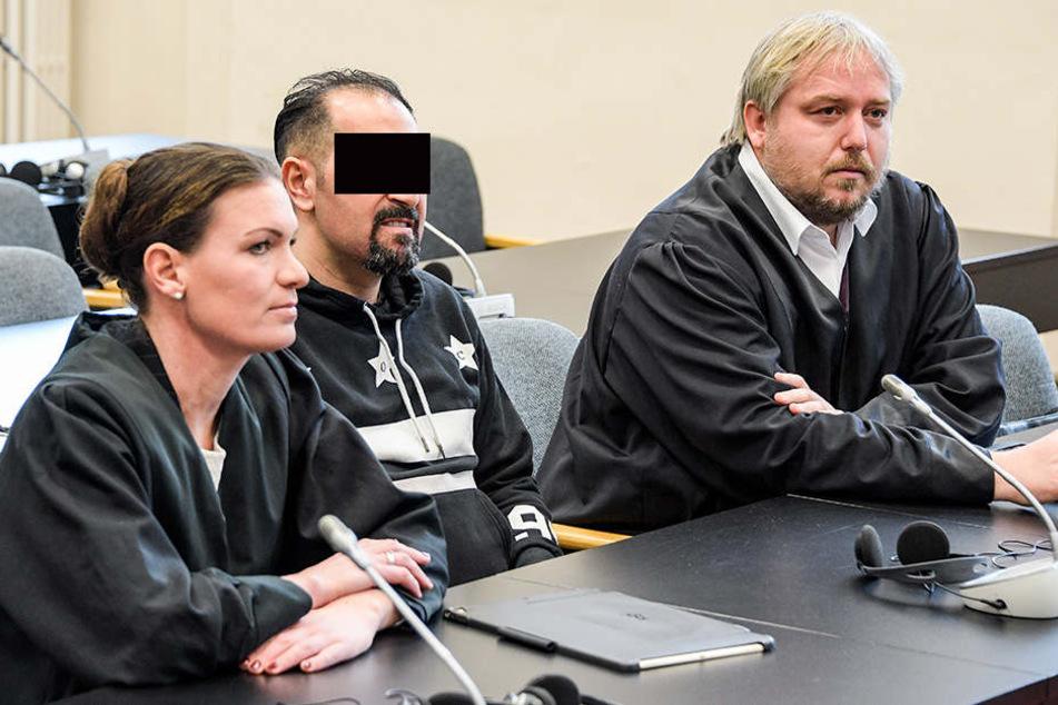 Der 30-jährige Angeklagte wartet zwischen seinen Anwälten Christian Lange (r) und Svenja Gruhnwald im Strafgerichtsgebäude auf den Beginn der Verhandlung.