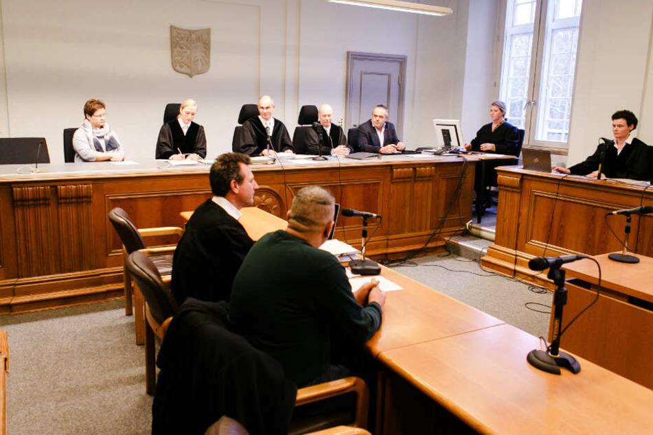 Die Prozessbeteiligten - Angeklagter vorne in der Mitte - sitzen im Gerichtssaal des Landesgerichts Kiel.