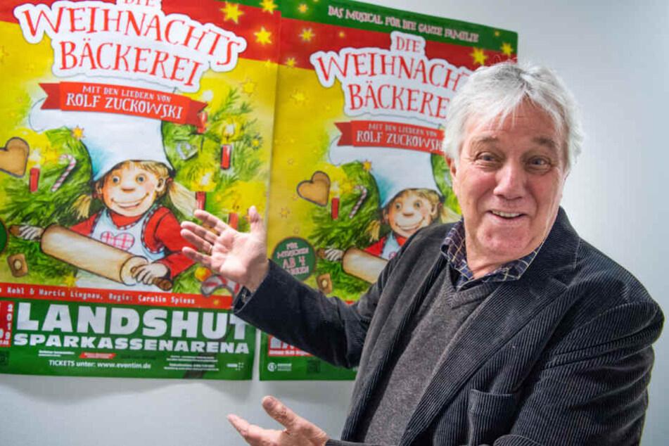 """Rolf Zuckowski, Liedermacher, zeigt auf Poster seines Musicals """"Die Weihnachtsbäckerei""""."""