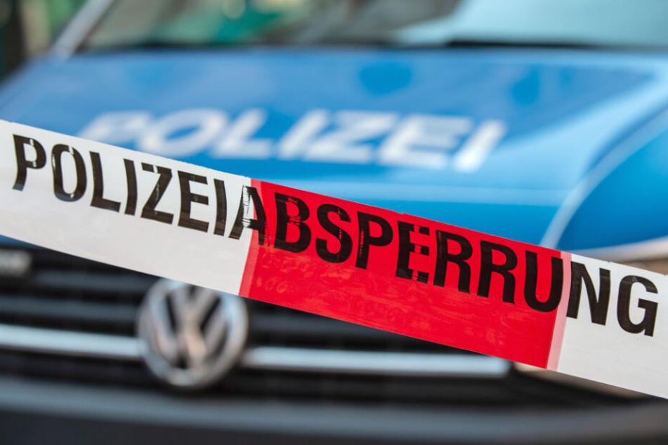 """Ein Flatterband mit der Aufschrift """"Polizeiabsperrung"""" ist vor einem Fahrzeug der Polizei zu sehen."""