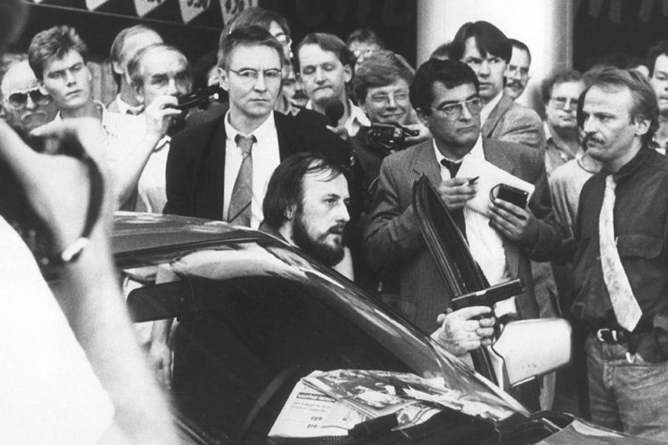 Mit einer Waffe in der Hand fordert der am Steuer des Fluchtfahrzeugs sitzende Hans-Jürgen Rösner am 18.08.1988 in der Innenstadt von Köln die umstehenden Journalisten und Passanten auf, den Weg frei zu machen.