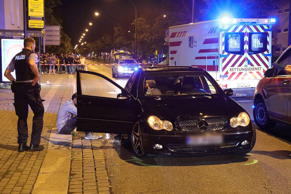 Ein Polizist steht auf einer abgesperrten Straße neben einem schwarzen Mercedes, der in einen Verkehrsunfall verwickelt ist.