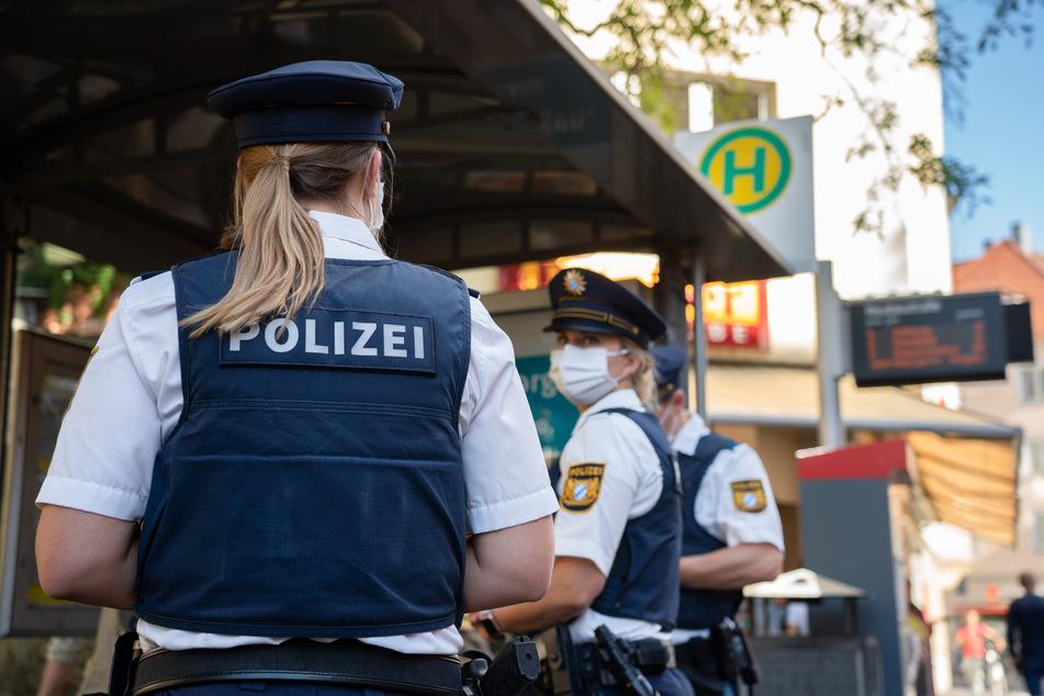 Würzburg: Drei Polizisten stehen an einer Tram-Haltestelle.