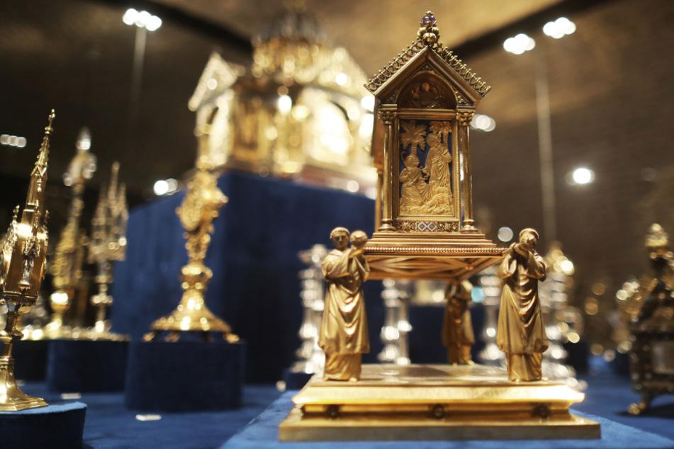 """Ein Reliquiar in Gestalt einer Reliquienprozession aus dem Jahr 1893 steht in einer Vitrine. Er ist Teil der Ausstellung """"Mittelalter 2.0 – Goldschmiedekunst des Historismus am Aachener Dom""""."""