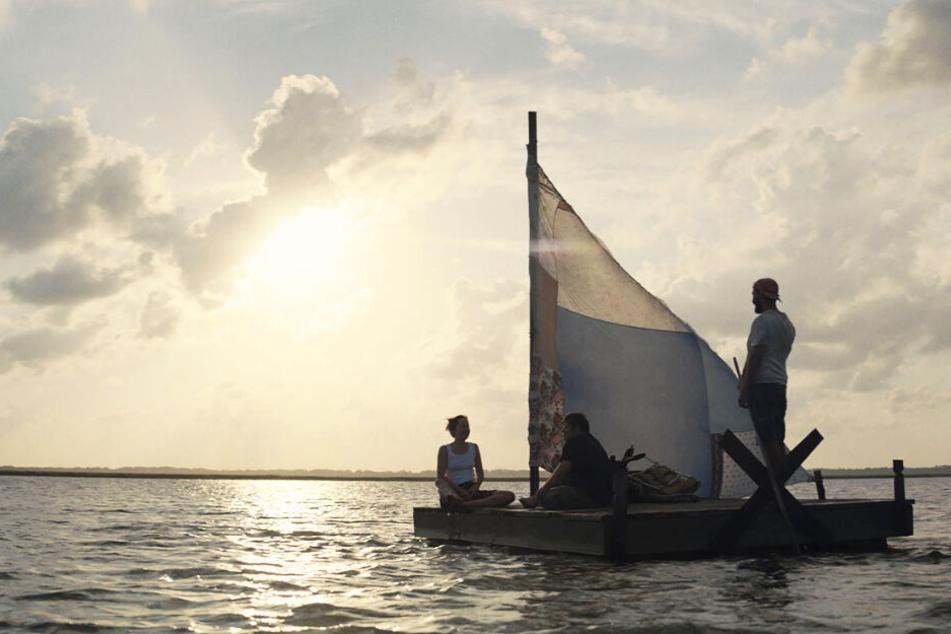 Tyler (r., Shia LaBeouf), Zak (M., Zack Gottsagen) und Eleanor (Dakota Johnson) sind auch mit einem Floß unterwegs.