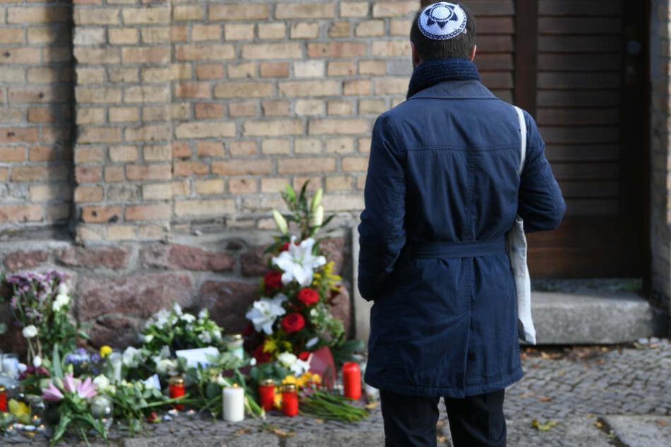 Ein Mann mit Kippa steht vor Kerzen und Blumen vor der Synagoge in Halle.