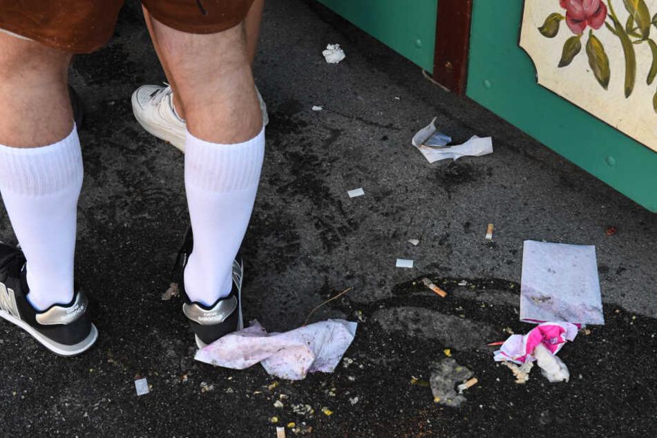 Müll liegt am Boden neben einem Verkaufsstand auf der Wiesn.