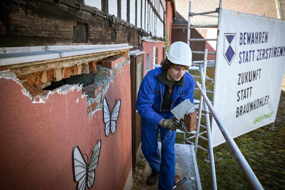 Aktivisten von Greenpeace reparierten am Montag Häuser in Pödelwitz, die der Mibrag gehören und sorgten so für einen Polizeieinsatz.