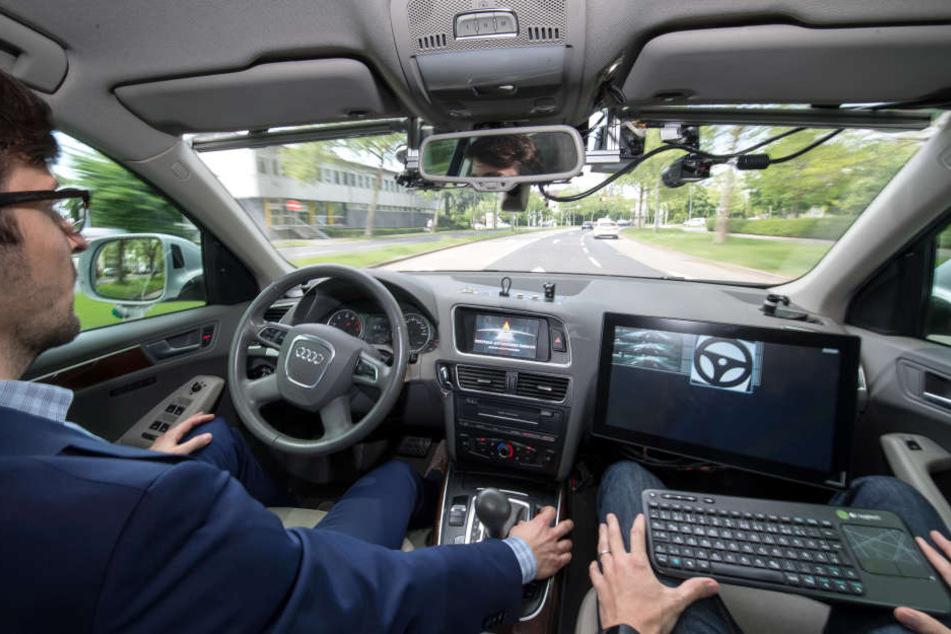Ein selbstfahrendes Auto des Forschungszentrumes Informatik fährt während der Eröffnung des Testfelds Autonomes Fahren mit zwei Entwicklern autonom im Straßenverkehr.