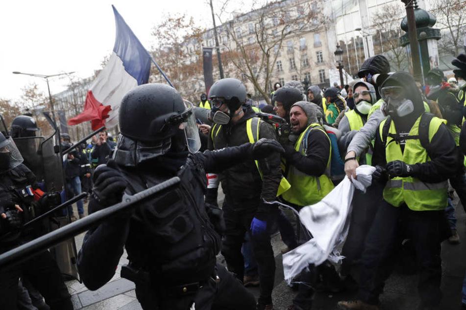 """In Paris setzt ein Polizist einen Schlagstock gegen Demonstranten der """"Gilets Jaunes"""" (Gelbwesten) ein."""