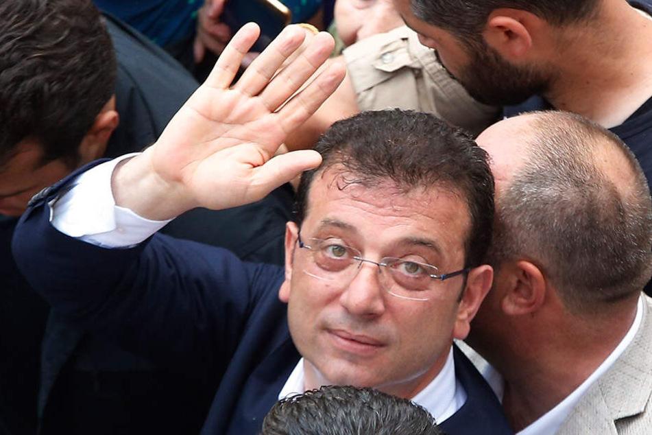 Wahlsieger Ekrem Imamoglu winkt seinen Unterstützern zu.