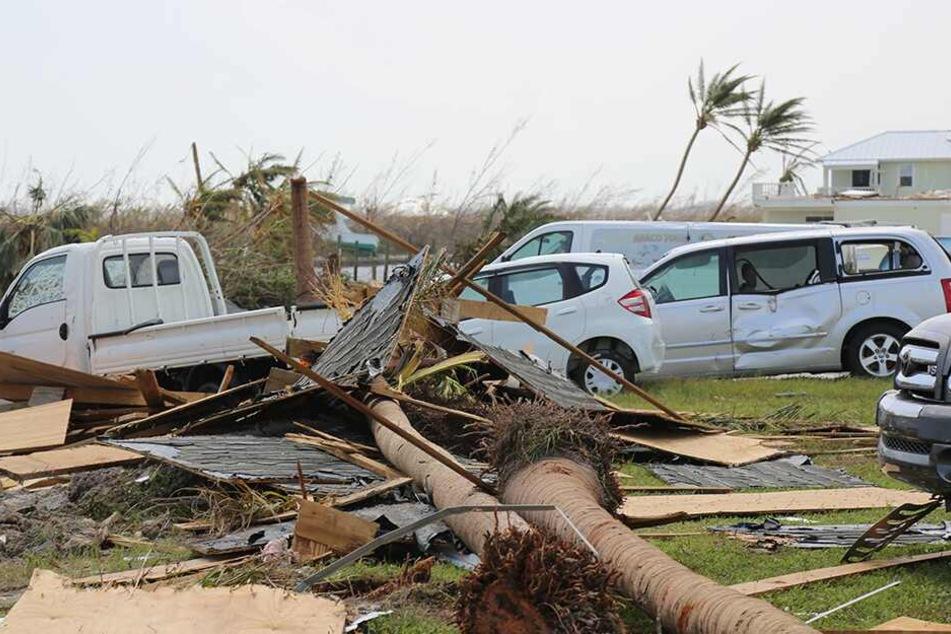 Zerstörungen durch den Hurrikan Dorian im Marsh Harbour auf Great Abaco Island. Autos und Lastwagen sind nach dem Sturm unter Palmen, Schutt und Trümmern begraben.