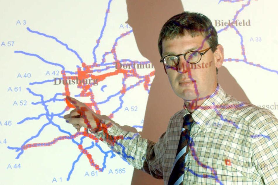 Stauforscher Michael Schreckenberg vor einer Projektion, die Messpunkte auf den nordrhein-westfälischen Autobahnen zeigt.