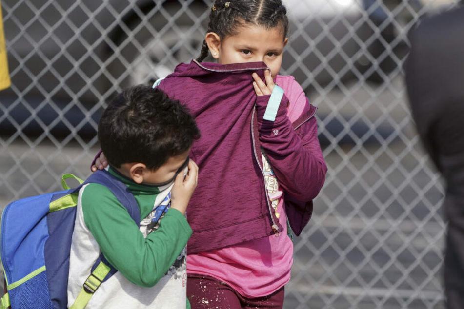 Zwei Kinder verlassen eine Schule und bedecken Nase und Mund.