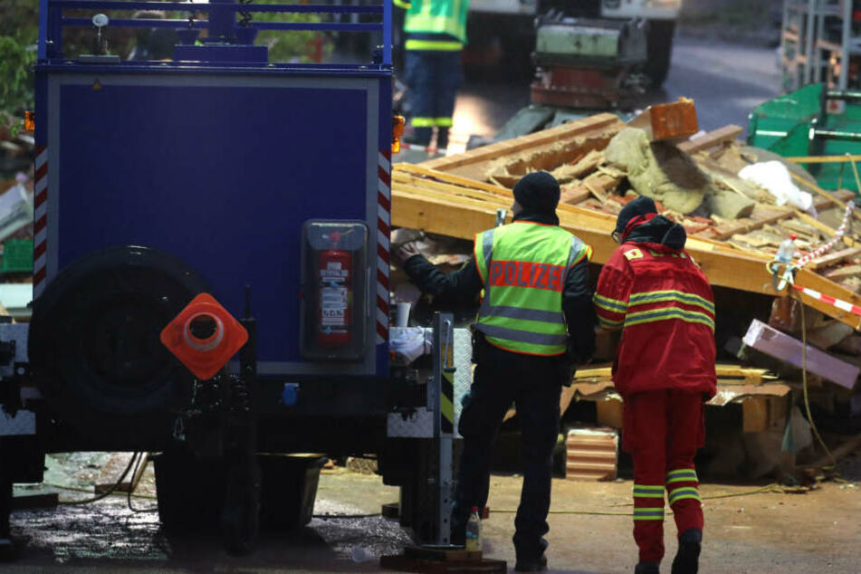 Hilfskräfte stehen bei der Suche nach Verschütteten vor Trümmern eines explodierten Wohnhauses.
