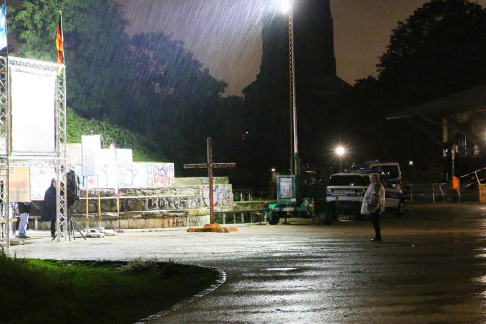 Bei strömenden Regen steht ein Pegida-Anhänger bei der Kundgebung im Görlitzer Park.
