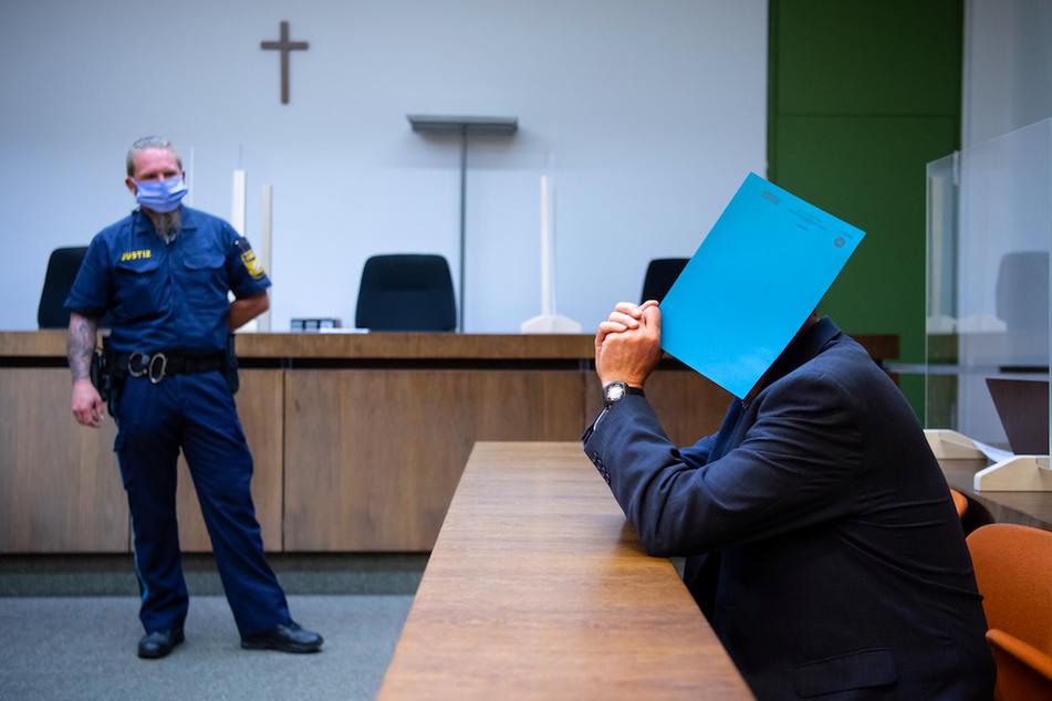 Der wegen sexuellen Missbrauchs von Kindern und Schutzbefohlenen sowie sexueller Nötigung angeklagte Mann (r) sitzt vor Prozessbeginn im Landgericht auf seinem Platz und hält sich einen Ordner vor das Gesicht.