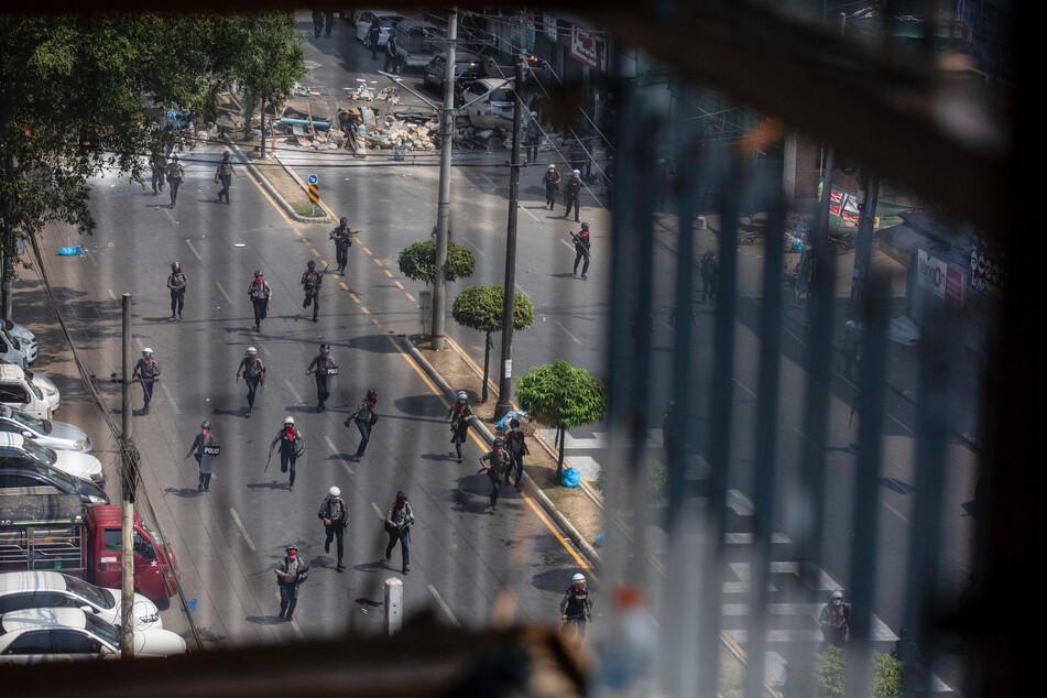 Polizisten laufen bei einem Protest gegen den Miltärputsch Demonstranten nach.