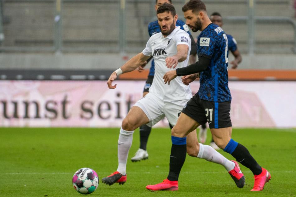 Daniel Caligiuri (l.) von Augsburg und Herthas Marvin Plattenhardt kämpfen um den Ball.