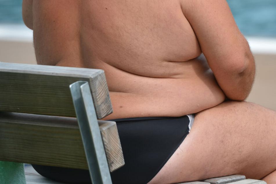 Ein übergewichtiger Mann sitzt am Strand.