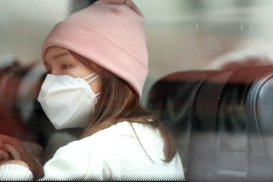 Eine Frau sitzt mit Mundschutz in einem Bus in China.