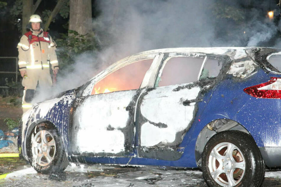 Ein Feuerwehrmann betrachtet ein ausgebranntes Auto am Kiehlufer in Berlin-Neukölln.