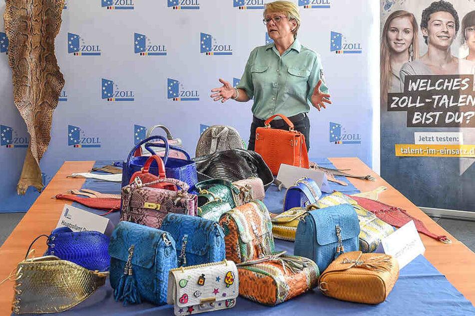 Heike Wilsdorf (50) vom Hauptzollamt Dresden zeigt Handtaschen und Gürtel die am Flughafen Leipzig beschlagnahmt wurden.